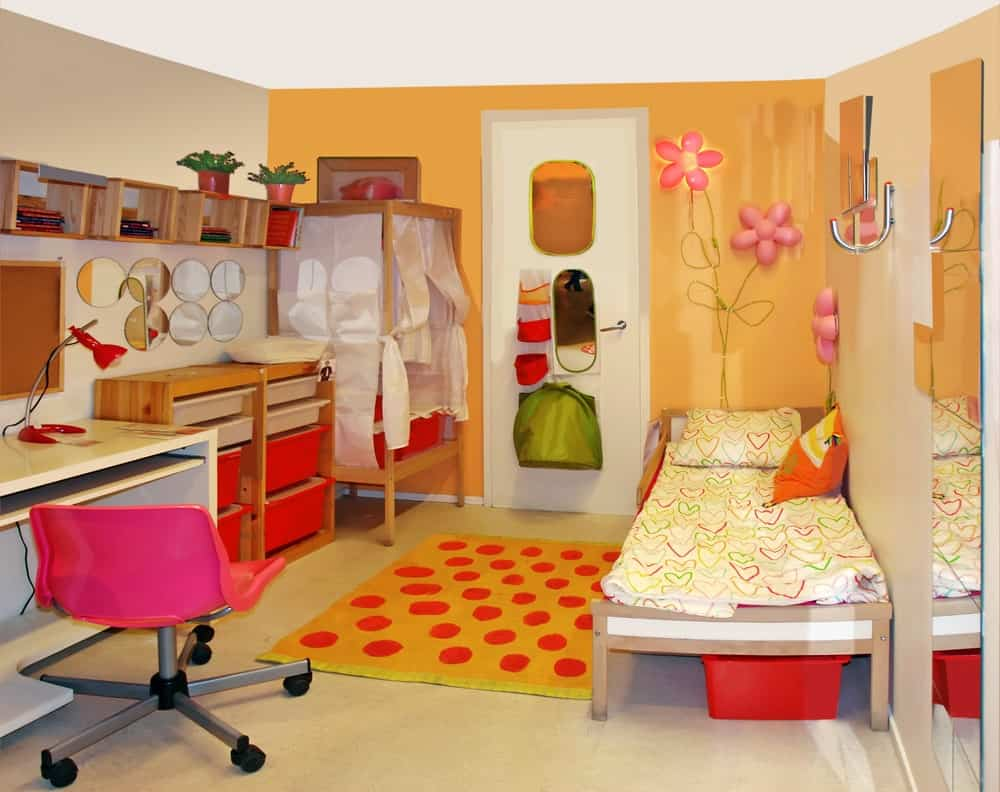 Girl's bedroom decorated with mirrors and floral lamps mounted on the orange wall. It has wooden toy storage, a stylish desk with pink swivel chair and a single bed with a dotted area rug on the side.