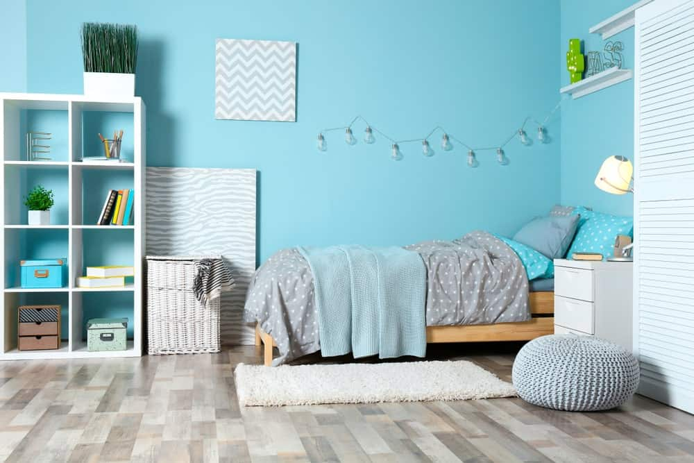 Blue bedroom showcases an open shelving and a wooden bed dressed in dotted bedding. It includes white nightstand and louvered cabinet along with a white shaggy rug and knitted ottoman.