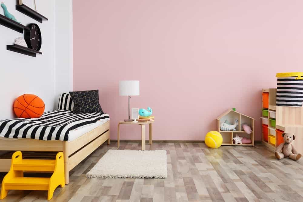 A white shaggy rug lays on the vinyl flooring in this kids bedroom with a wooden bed dressed in striped bedding and a spacious play area on the side showcasing a toy storage with multicolored bins.
