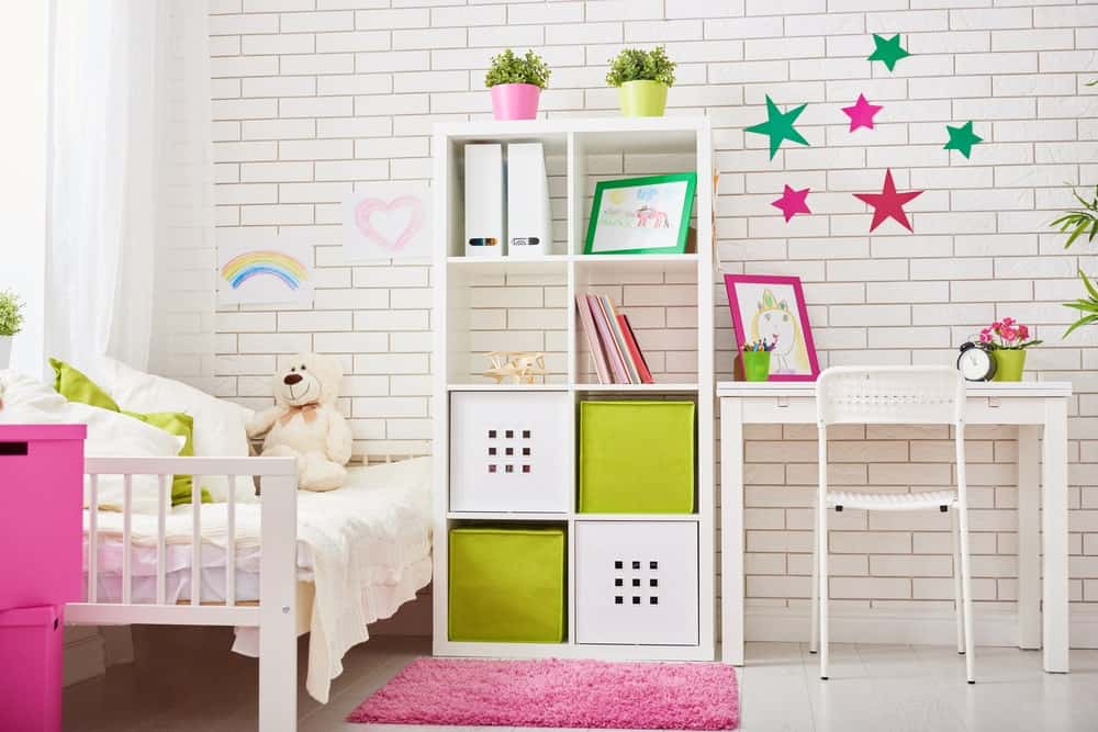 A charming bedroom designed with kids artwork and star stickers glued on the white brick wall. It has a white bed and shelving unit along with a study desk paired with a perforated chair.