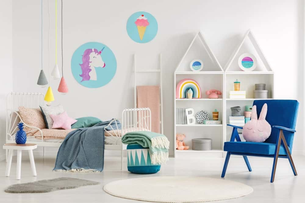 White bedroom filled with loads of cuteness from the wall arts and pendant lights that hung beside the white metal bed. It includes open shelvings and a blue armchair topped with a bunny head pillow.