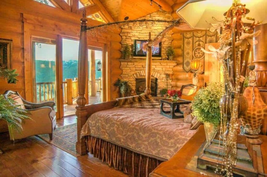 Large master bedroom with rustic walls, ceiling and flooring. It has an elegant bed setup and a stone fireplace with a TV on top. The warm lighting looks so perfect together with the bedroom's rustic style.