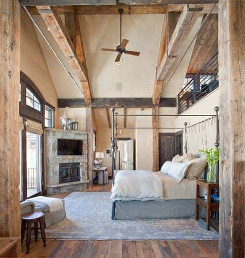 Rustic master bedroom featuring a tall ceiling with large rustic beams. The room also features hardwood flooring topped by a large gray rug along with a fireplace with a widescreen TV on top.