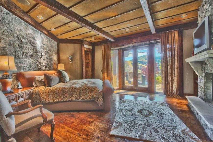 Large rustic master bedroom with a stone wall, hardwood flooring and a rustic ceiling. The room has a large cozy bed lighted by two table lamps and a large stone fireplace.