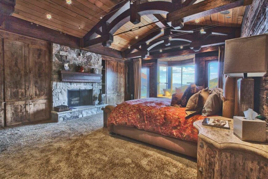 Large rustic master bedroom featuring a stunning wooden ceiling with large beams along with carpeted flooring. The room offers rustic furniture along with a large fireplace.