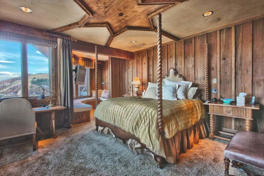 Master bedroom featuring a stylish rustic-design on the ceiling. It has wooden walls and thick carpet flooring. The room offers a cozy bed and a rustic office desk area, along with a sunroom.