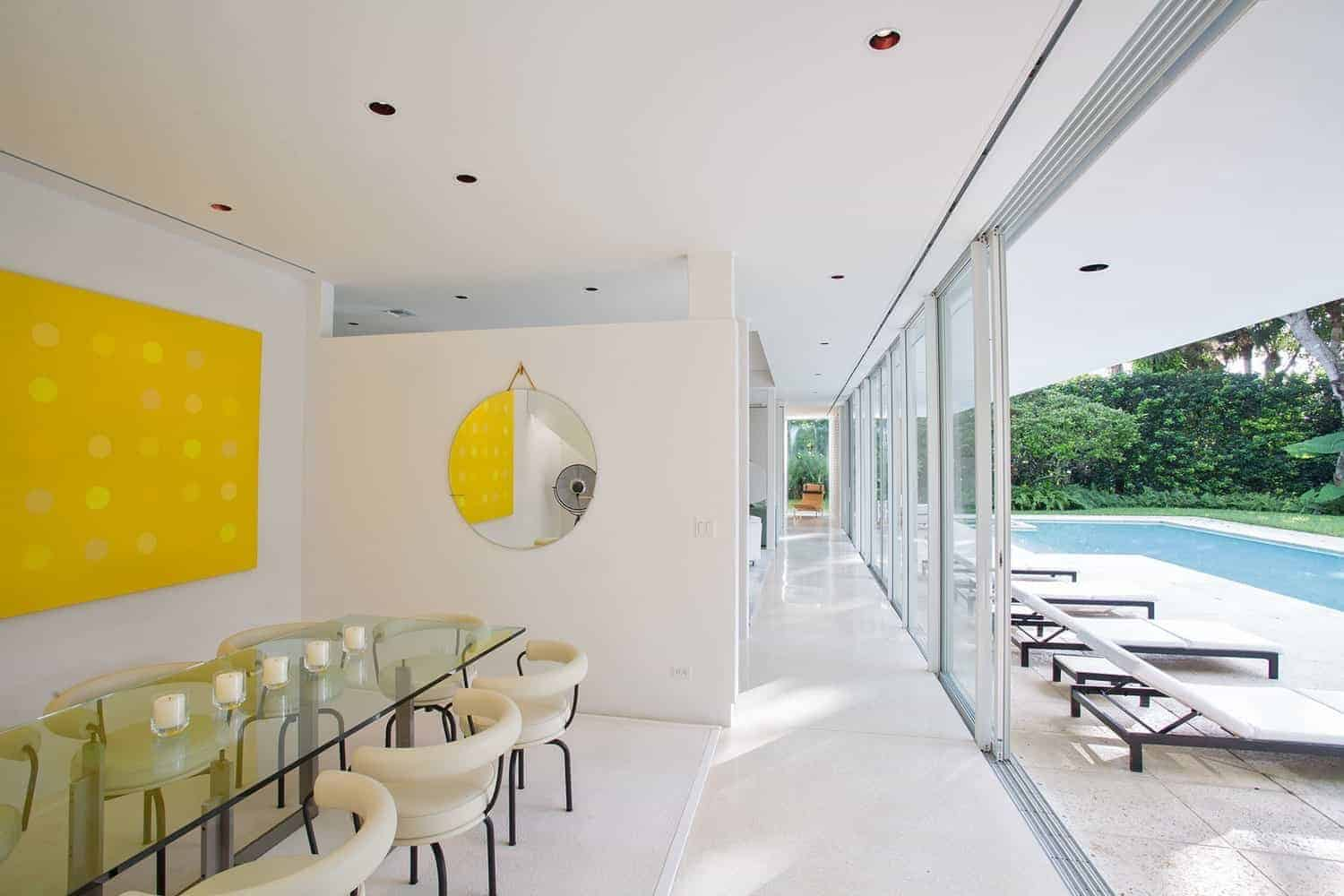 The glass-top rectangular dining table is a perfect match for the sliding glass doors that open to a poolside scenery. This gives a sense that the dining room is bigger that it seems. The addition of the yellow abstract painting complements the beige modern dining chairs.