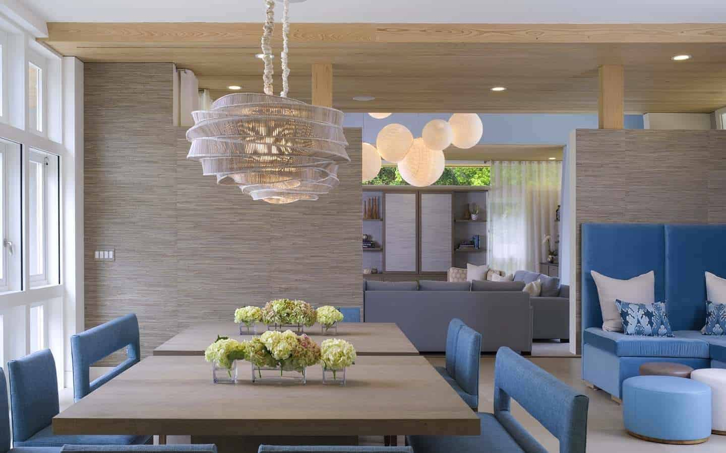 This airy and bright kitchen has a bare wooden ceiling paired with brown wooden walls that match the square dining tables topped with a peculiar pendant light with a rustic hood. These are contrasted by the blue velvet cushions of the chairs.