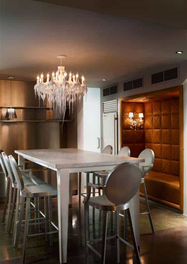 The stainless steel modern stools are paired with a tall rectangular table that has a white marble top contrasting the dark hardwood flooring but matches with the white chandelier that has a peculiar design that make it seem like a melting cake frosting.