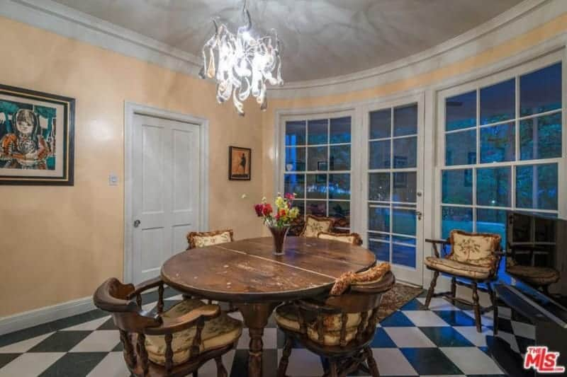The black and white checkered flooring design goes well with the French glass door and windows that have white frames matching the door and ceiling that are complemented by the yellow walls and the wooden dining set that has an antique quality to it.