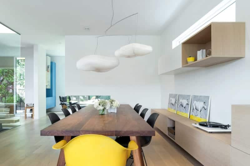 The wooden rectangular dining table is topped with a couple of peculiar white pendant lights that look like clouds. This goes well with the light hues of the walls and ceiling that make it seem like the clouds are floating in the sky over the hardwood flooring matching the cabinets and shelves.