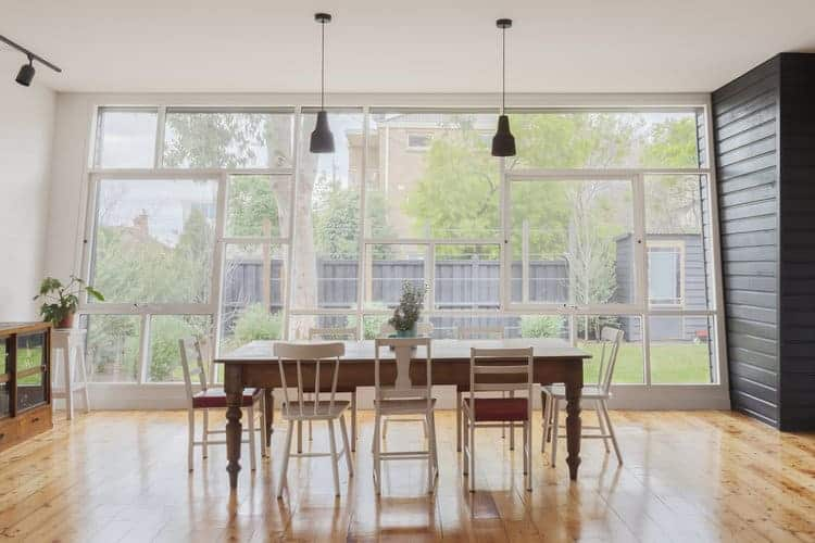 This is a medium-sized dining room with an abundance of natural lights on its hardwood flooring due to the glass wall with white frames that match the variety of white wooden chairs surrounding the wooden rectangular table that fits with the flooring.