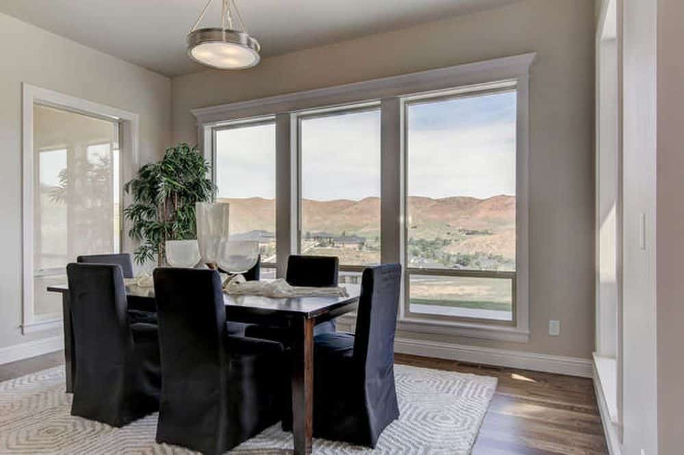 The dining chairs of this medium-sized dining room has black velvet slip covers that stand out against the light gray patterned area rug and the beige walls that are dominated by tall windows that showcase a nice mountain view.