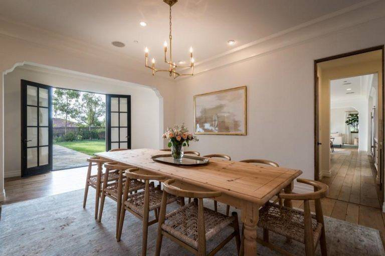 The rustic wooden chairs with woven wicker seats fit perfectly with the wooden dining table topped with a small lovely golden chandelier that casts warm yellow light on the beige ceiling and walls adorned with a colorful painting.