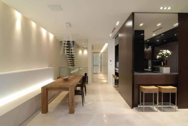 This bright medium-sized dining area beside the kitchen has beige marble flooring and beige walls that has a built-in white bench paired with the wooden dining table. There are modern accents due to the back lighting of the walls and bench together with the recessed lights of the white ceiling.