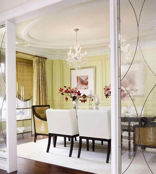 This dining room is separated from the rest of the house by frosted glass walls with white frames that match the white cushioned dining chairs, area rug on the dark hardwood flooring and the white ceiling with an elliptical design that supports a white chandelier in the middle.