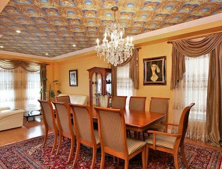 The warm yellow walls that are accented with classic paintings match with the yellow details of the complex and peculiar design of the ceiling. It has a majestic white crystal chandelier that brightens up the wooden dining set and colorful patterned area rug.