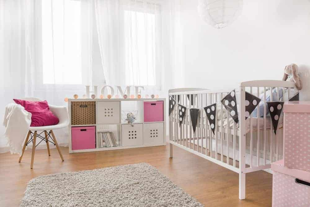Black dice garland flags surround the white crib in this airy nursery boasting a modern white chair and open shelving filled with storage boxes.