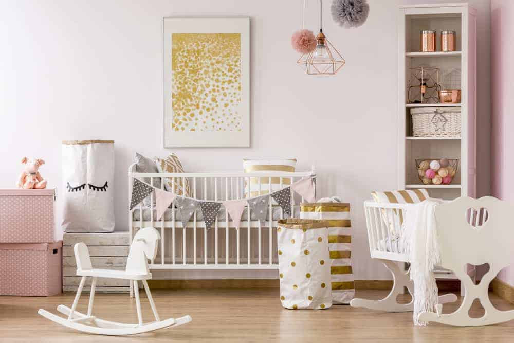 Gorgeous nursery designed with a copper geometric pendant and stunning gold artwork mounted above the white crib that's decorated with garland flags.