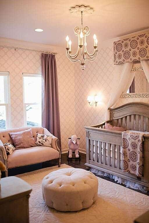 A round tufted ottoman sits on the textured area rug in this nursery with a classy pink chair and natural wood crib lighted by wall sconce and candle chandelier.