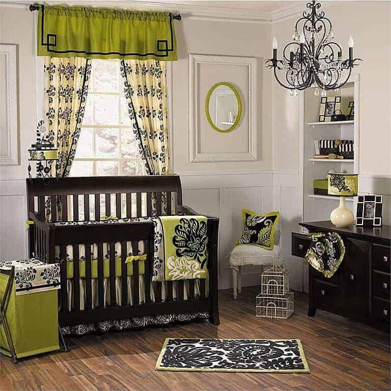 Sophisticated nursery illuminated by a black ornate chandelier and a green printed lampshade that sits on console table complementing the dark wood crib.