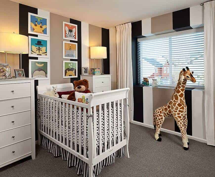 This nursery is decorated with a giraffe plush toy and animal artworks mounted on the striped wall. It has a skirted crib flanked by white drawers and drum table lamps.