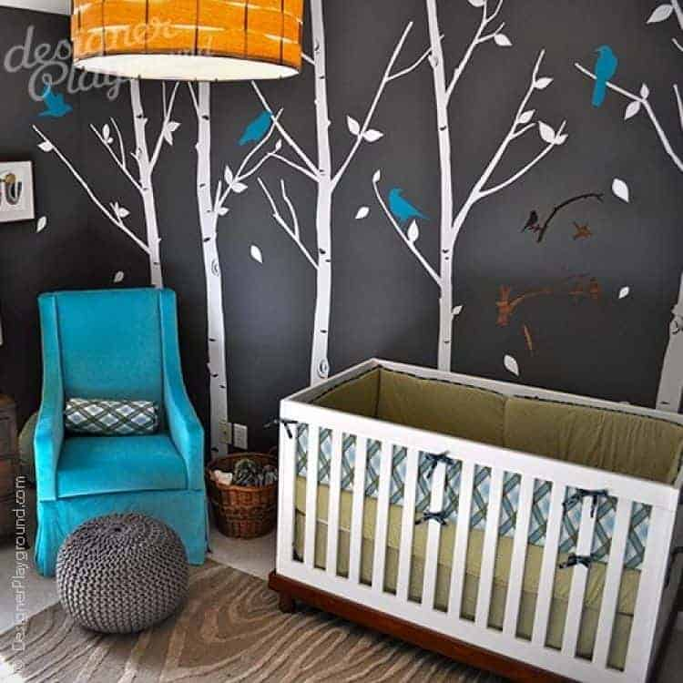 Clad in trees and birds wallpaper, this nursery boasts a white crib and blue skirted armchair paired with a round knitted ottoman on a textured area rug.