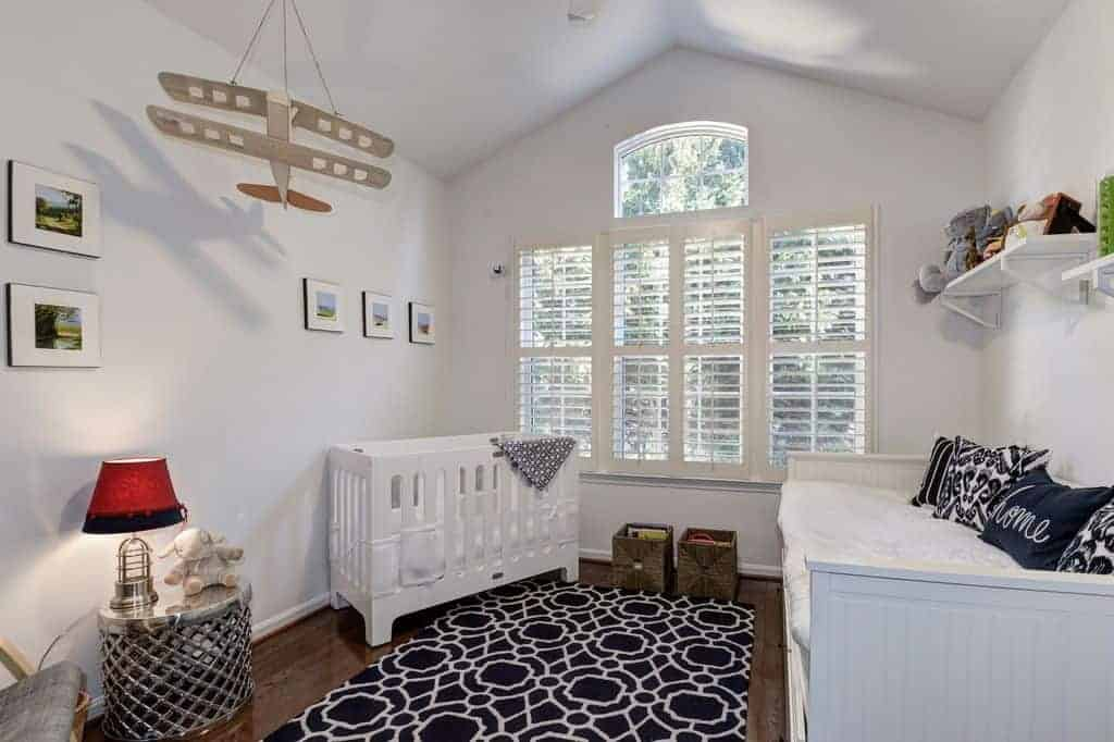 White nursery contrasted with black patterned rug and pillows that lay on the beadboard sofa. It has a sleek crib and stylish round table topped with a red lampshade.