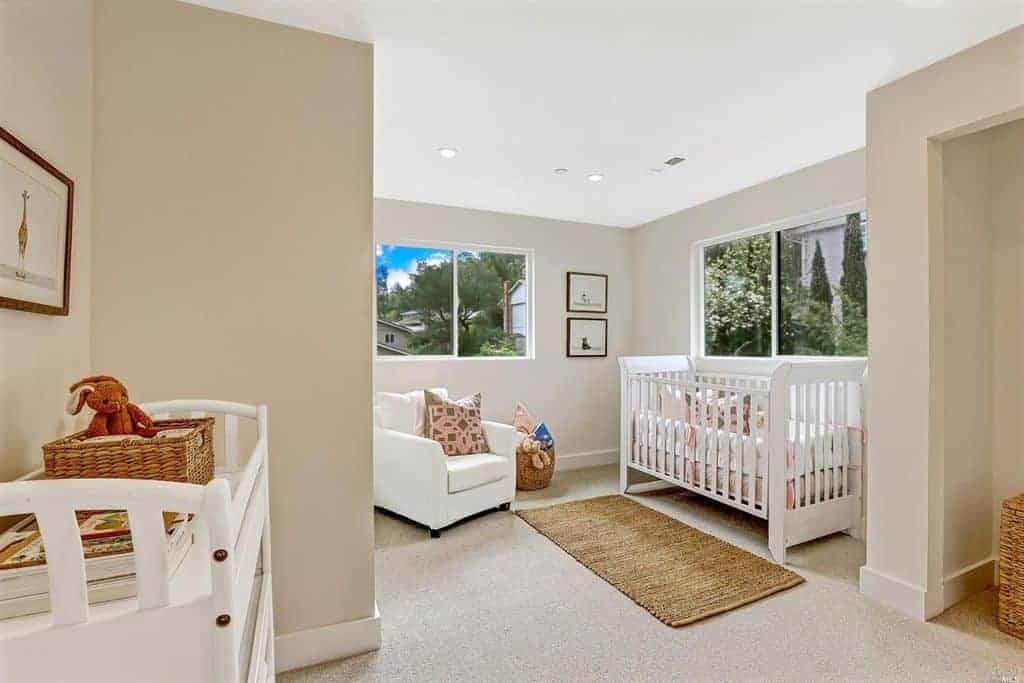 Taupe nursery with carpet flooring and glazed windows overlooking the outdoor greenery. It has white furnishings and a jute runner that complements the rattan baskets.