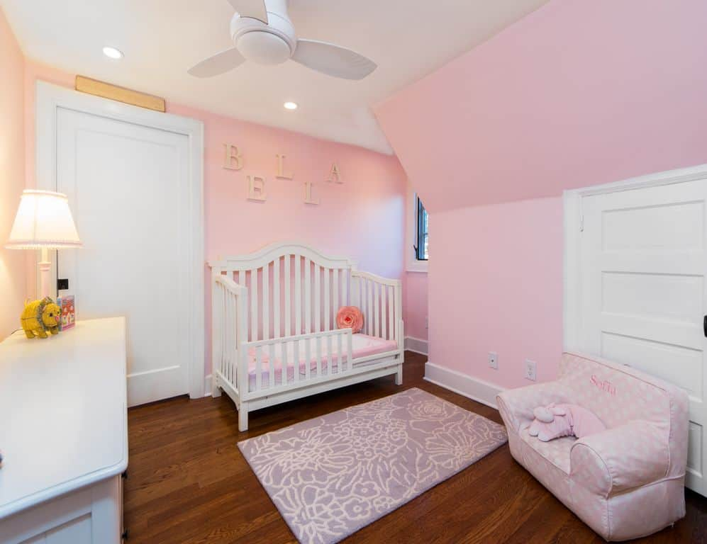 A traditional table lamp sits on the white cabinet in this pink nursery showcasing a charming crib and dotted armchair with a purple floral rug in the middle.