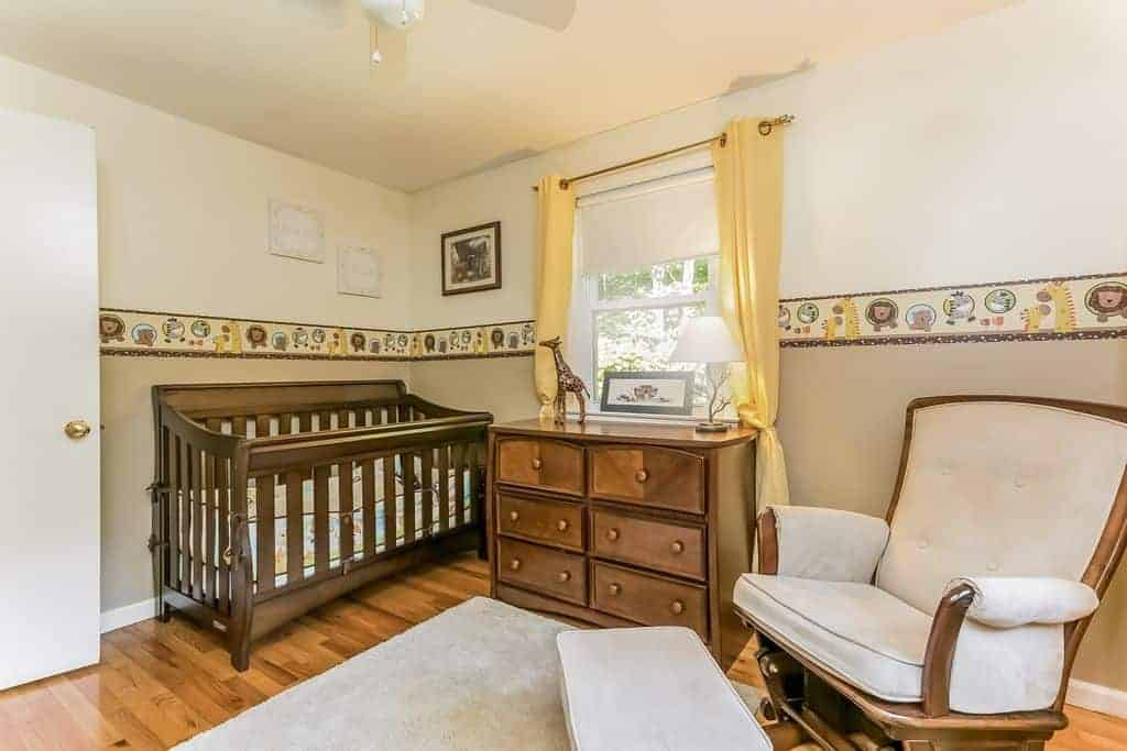 This nursery is furnished with a wooden crib and cabinet along with a cushioned armchair that's paired with a matching ottoman sitting on a gray rug.