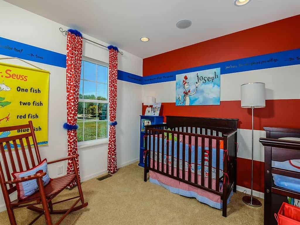 This nursery features a wooden rocking chair and skirted crib lighted by a chrome floor lamp. It has carpet flooring and white framed windows dressed in red dotted draperies with blue fur accents.