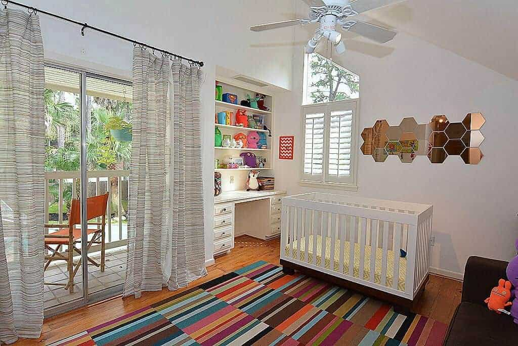 A colorful striped rug adds a striking accent in this white nursery with a desk and stylish honeycomb mirror mounted above the sleek crib. It has built-in shelving and glass slider that leads out to the balcony.