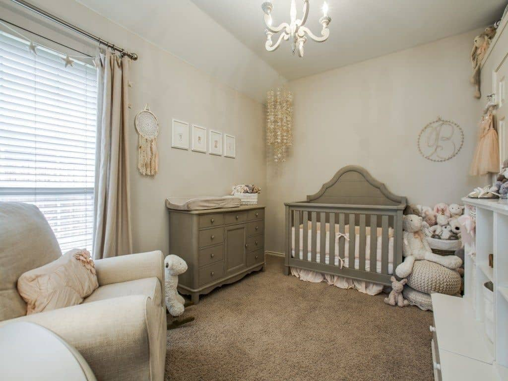 Boho style nursery with a lovely chandelier, a comfy armchair and wooden dresser complementing with the shiplap crib over carpet flooring.
