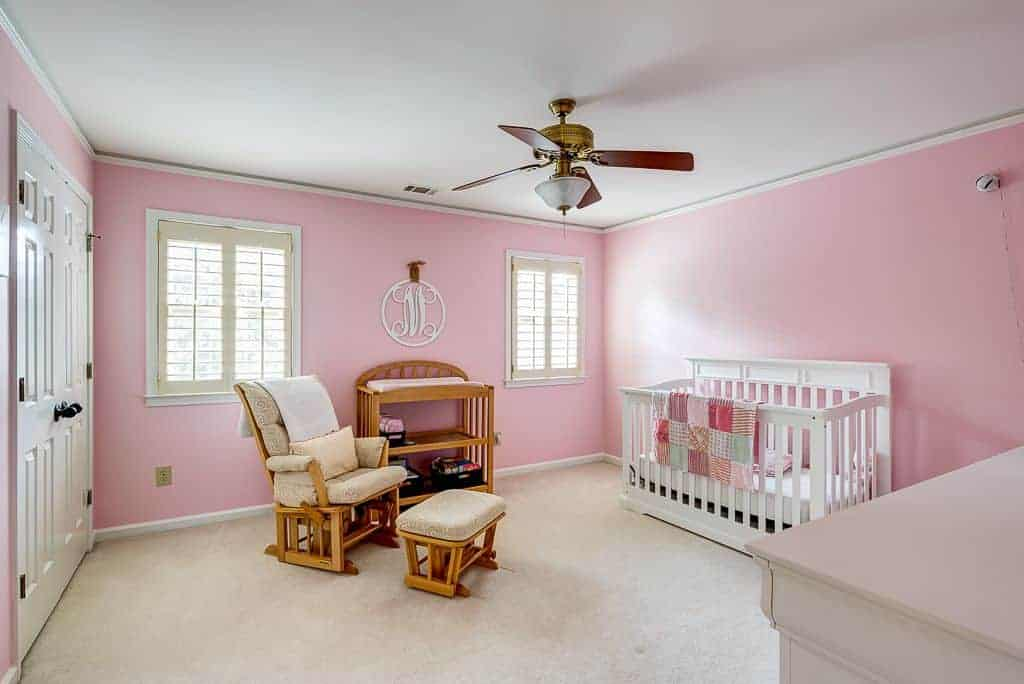 Pink nursery with a white crib and wooden shelving complementing with the cushioned armchair and matching ottoman. It has a classic ceiling fan and white framed windows enclosed in cream shutters.