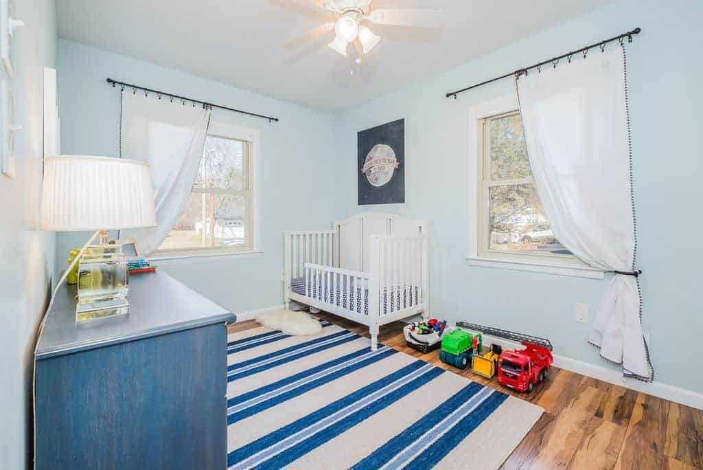 Bright nursery boasts a white crib and blue cabinet topped by a table lamp with pleated shade. It includes a white ceiling fan with lights and a striped rug that lays on the hardwood flooring.