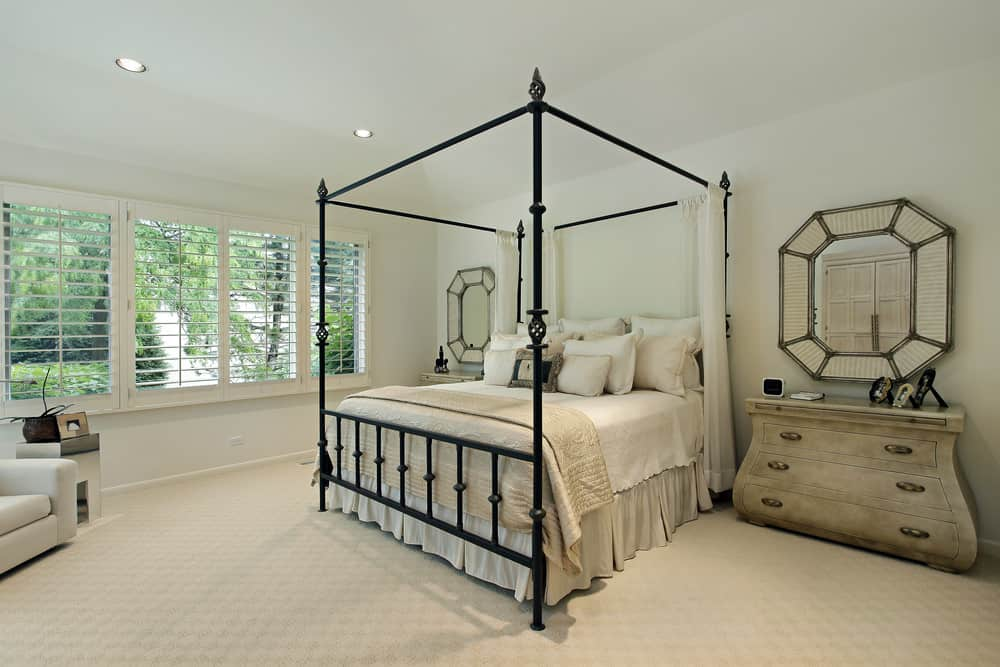 Large Country style master bedroom featuring classy carpet flooring and white walls. It has a nice bed along with rustic side tables.