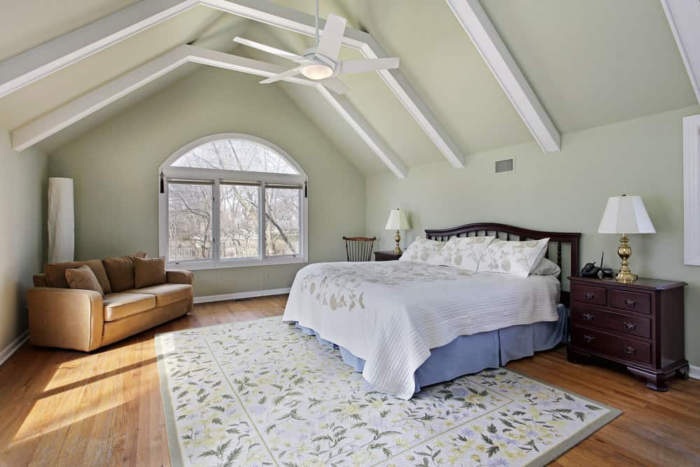Spacious master bedroom featuring hardwood flooring and a vaulted ceiling with beams. It offers a large bed along with a brown couch in the corner.