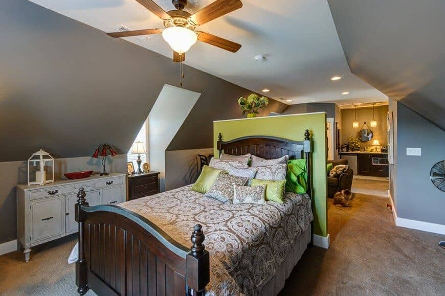 Country style master bedroom with gray walls and carpet flooring. The room has a double-sized bed with a wooden frame.