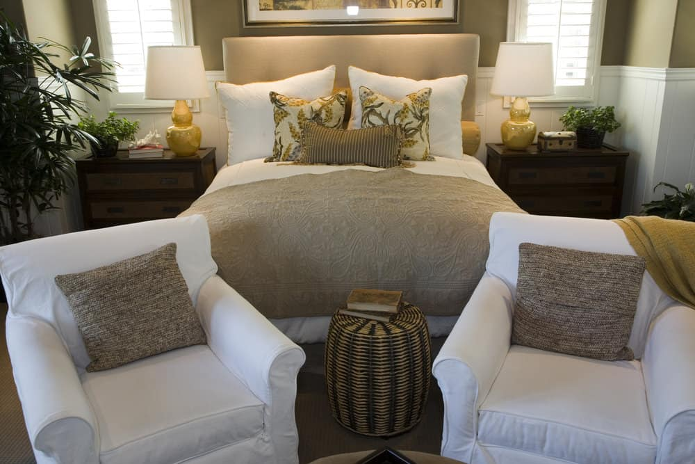 A focused look at this master bedroom's large bed setup with a pair of white seats at the edge of the bed.