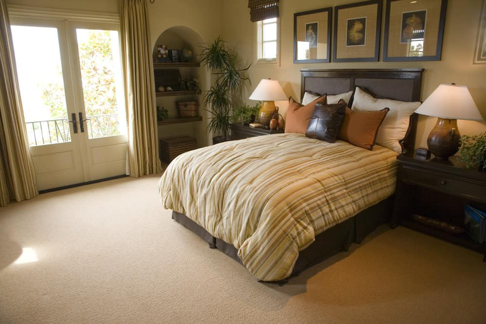 Spacious master bedroom featuring a classy bed setup along with built-in shelving on the side. The room features a tall ceiling and carpeted flooring.