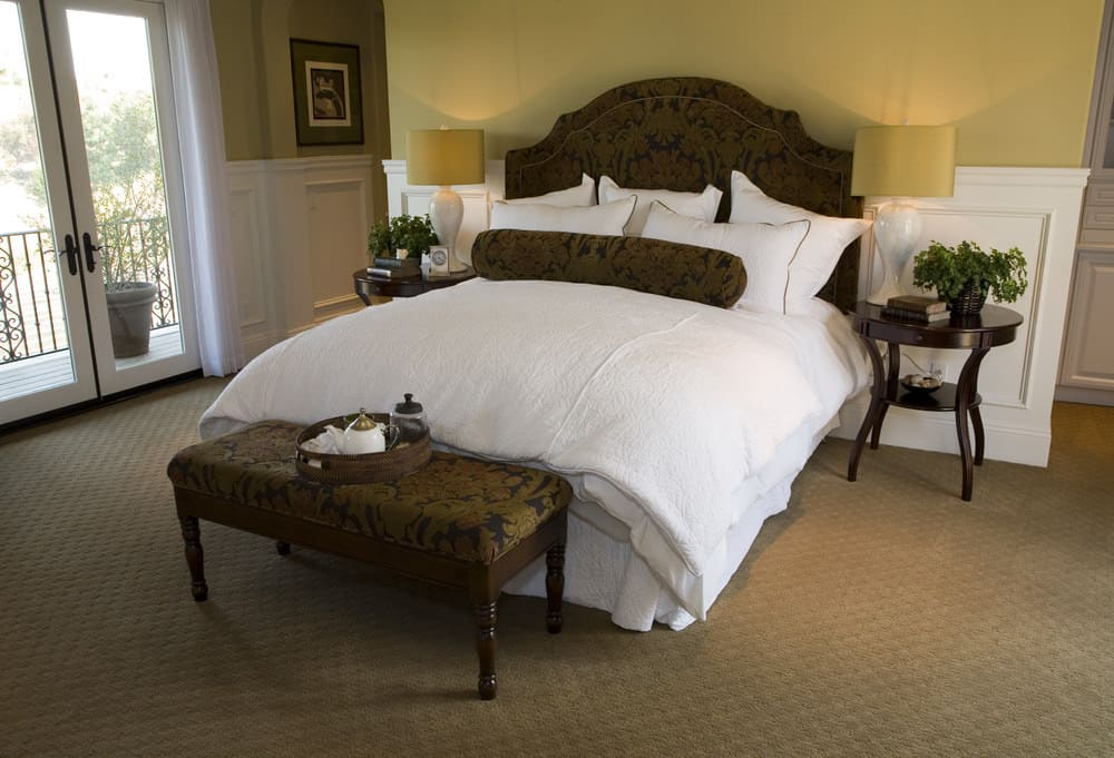 Large master bedroom featuring a large classy bed set on the room's carpet flooring and is surrounded by yellow walls.