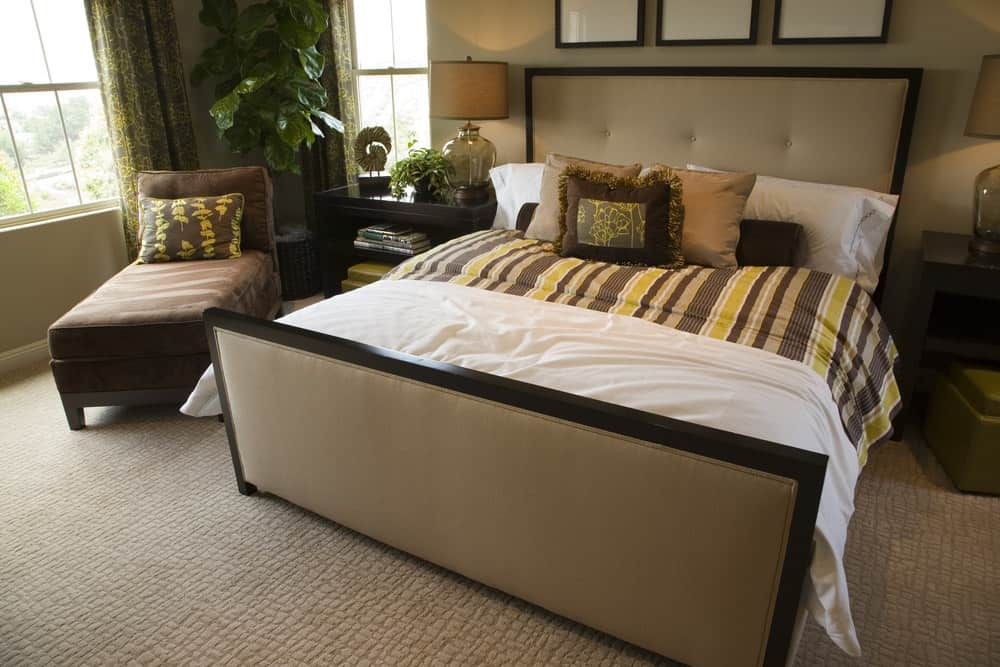 A focused look at this master bedroom's large bed setup lighted by table lamps on both sides. The room features indoor plants inside the room.