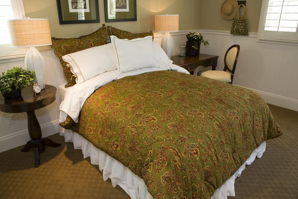 A focused look at this master bedroom's large classy bed lighted by table lamps on both sides. There's a small desk with a chair on the side of the bed.