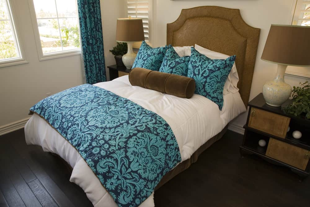 A focused shot at this master bedroom's classy double-sized bed with a blue accent lighted by brown table lamps matching the brown bed frame.