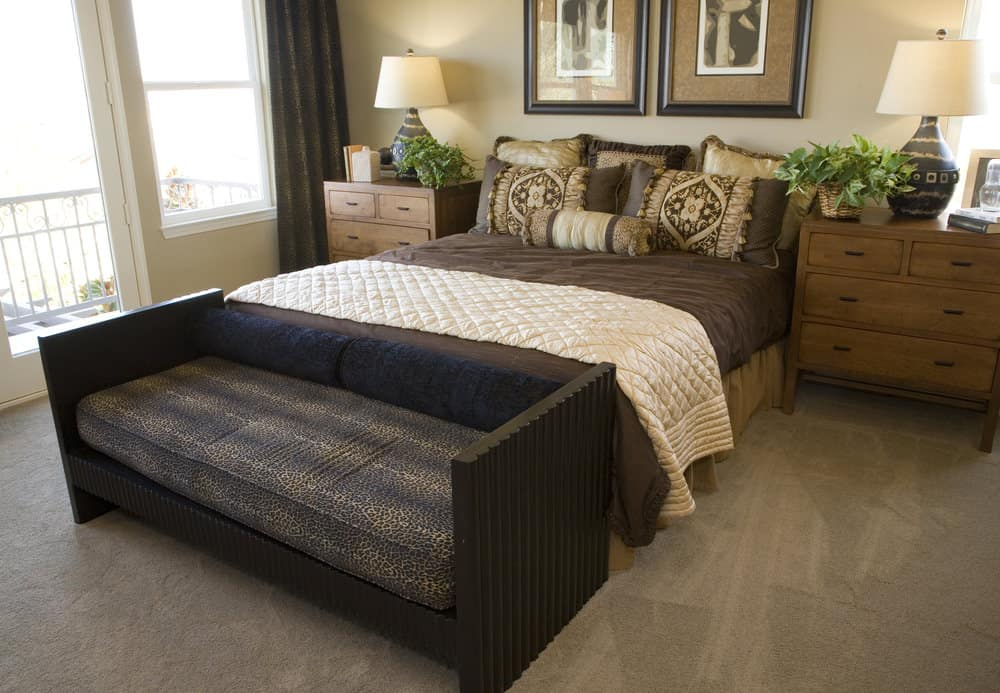 A close up look at this master bedroom's bed setup with a couch at the edge, set on the gray carpet flooring.