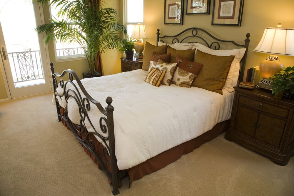 Master bedroom featuring a classy bed lighted by table lamps on both sides, set on the carpet flooring. The room offers its own balcony area.
