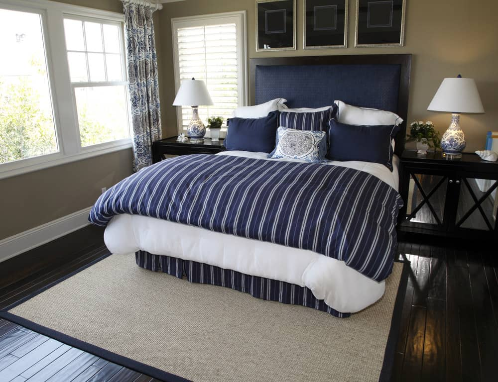 A focused shot at this master bedroom's navy blue bed setup with a brown area rug on top of the hardwood flooring.