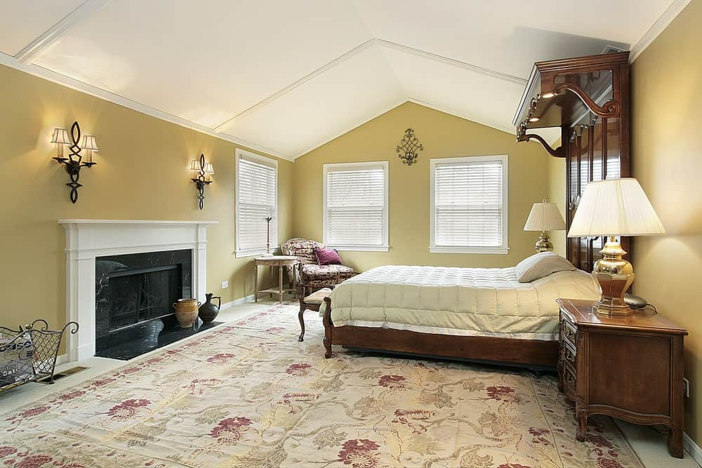 Large master bedroom featuring a vaulted ceiling and a large classy area rug. It has a luxurious large bed along with a large fireplace lighted by wall lights.
