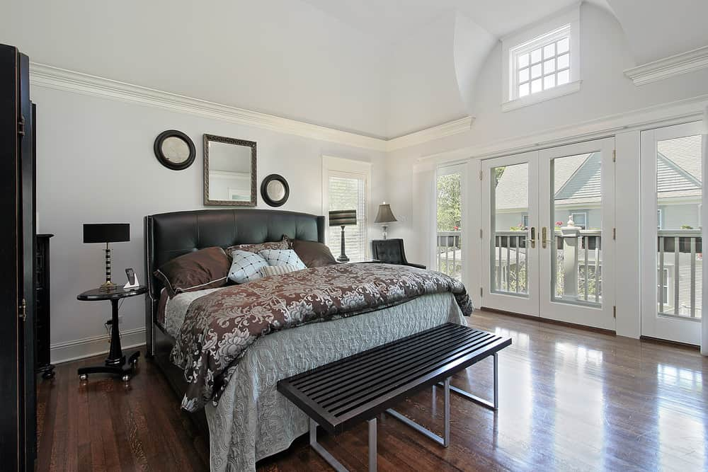 A spacious master bedroom featuring white walls, hardwood flooring and a tall ceiling. The room offers a large classy bed lighted by two table lamps.